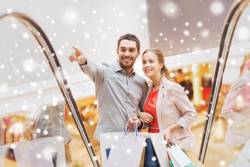 Koppla ihop med shoppingpåsar på rulltrappan i galleria royaltyfri bild