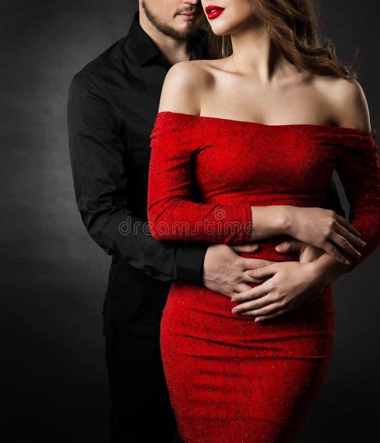 Koppla ihop modeskönhet, kvinna i röd klänning och den förälskade omfamnamannen royaltyfri bild