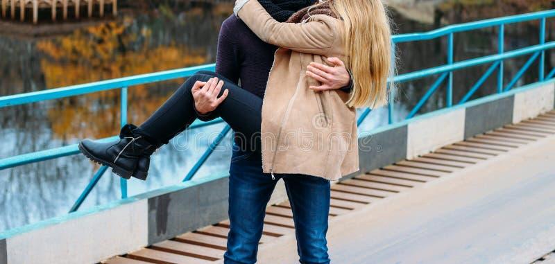 Koppla ihop på bron, grabben rymmer flickan i hans armar, kram, nära vattnet, hösten förälskelse och familj, ett datum i arkivfoto