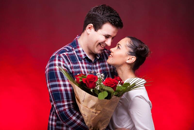 Koppla ihop på ett datum, medan kvinnan rymmer blommor i händer fotografering för bildbyråer
