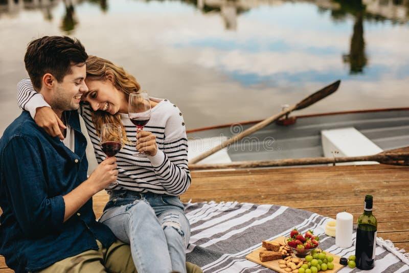 Koppla ihop på ett datum som tillsammans sitter bredvid en sjö som dricker vin royaltyfri foto