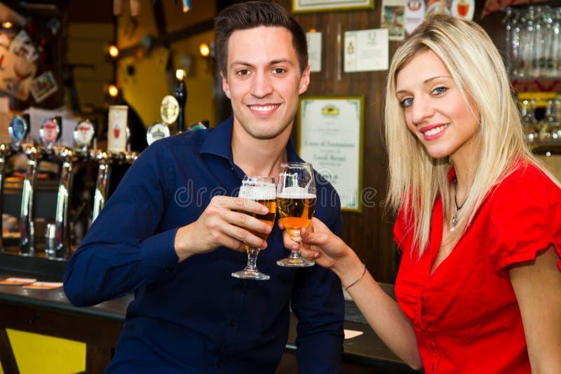 koppla ihop på ett datum som tycker om deras drink i en bar royaltyfri foto