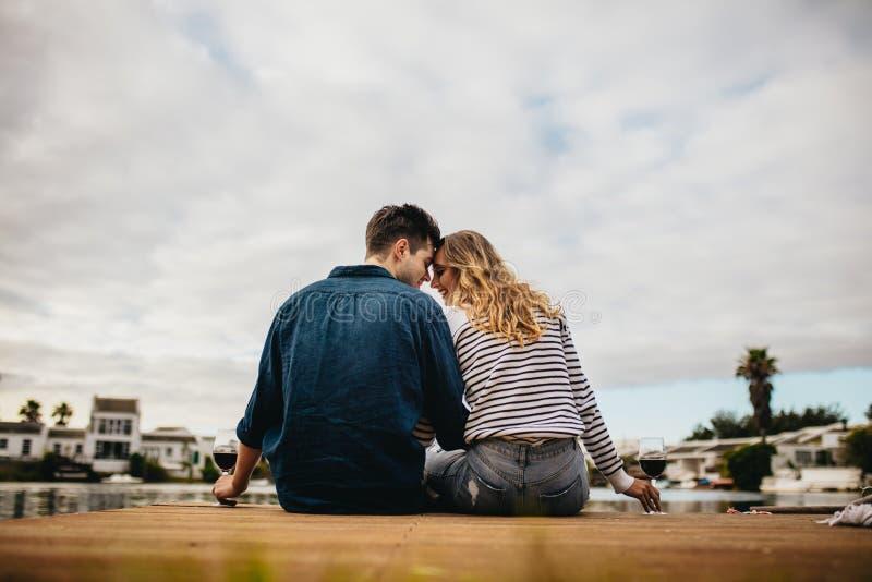 Koppla ihop på ett romantiskt datum som sitter nära en sjö royaltyfri foto