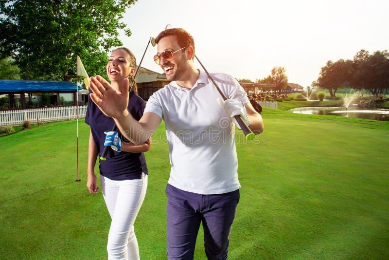 Koppla ihop på kursen som spelar golf och ser lycklig - bilden royaltyfria foton