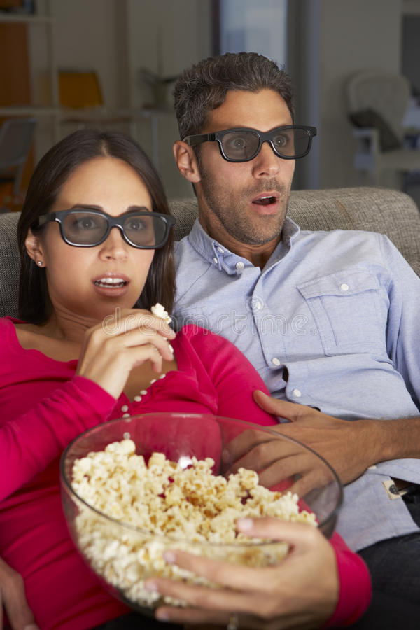 Koppla ihop på Sofa Watching TV som bär exponeringsglas som 3D äter popcorn fotografering för bildbyråer