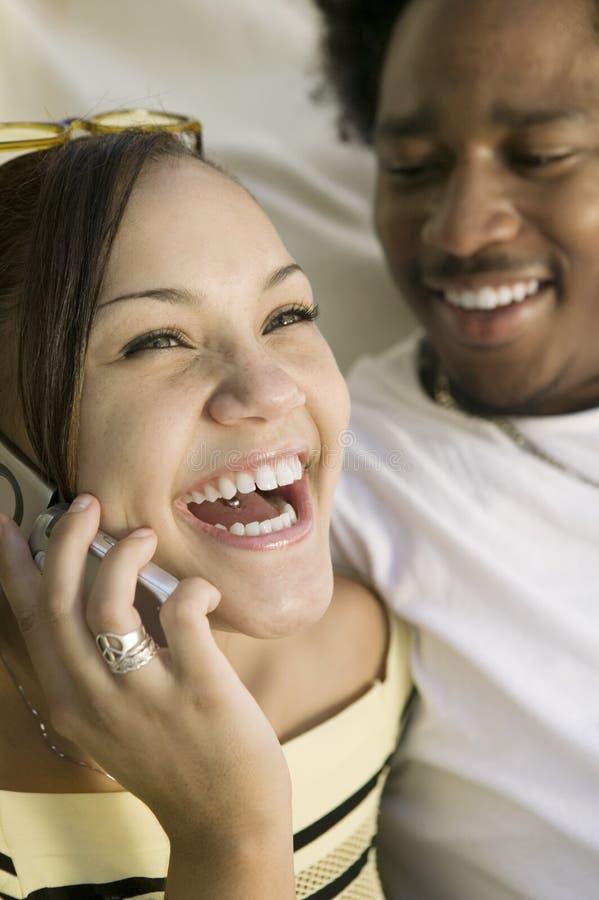 Koppla ihop på soffakvinnan på mobiltelefonen som tätt skrattar upp royaltyfri foto