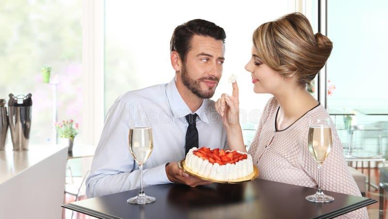 Koppla ihop på stången med mousserande vin och kakan, förälskelsebegrepp royaltyfria bilder