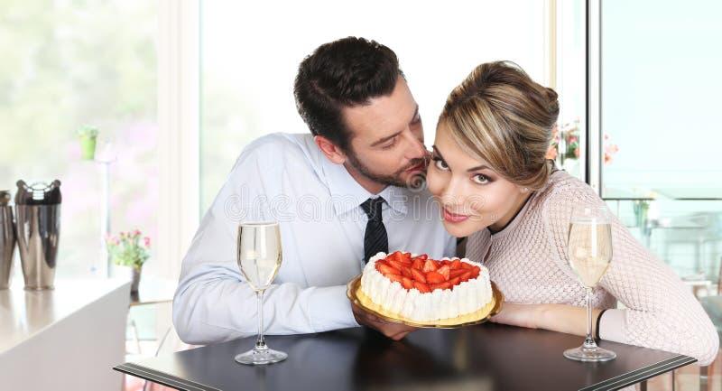 Koppla ihop på stången med mousserande vin och kakan, förälskelseconce arkivbilder