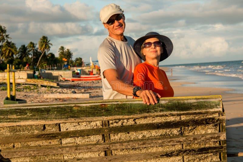 Koppla ihop på stranden nära solnedgång arkivfoton