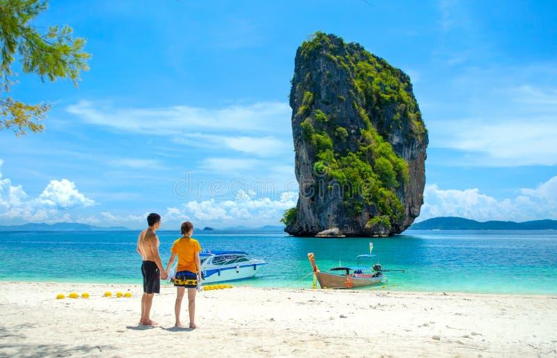 Koppla ihop på stranden som står rymma händer som ser den härliga havssikten på den Poda ön - Krabi Thailand arkivfoto