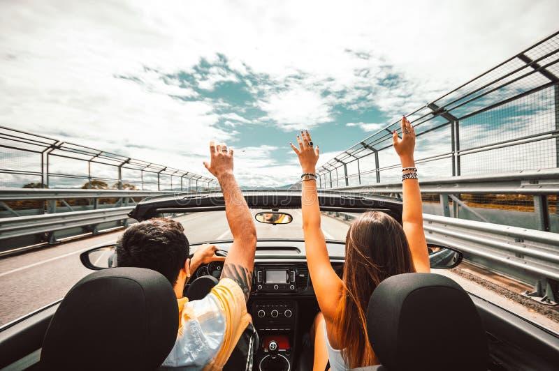 Koppla ihop på vägen på en konvertibel bil royaltyfria bilder