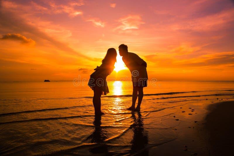 Koppla ihop p? stranden p? solnedg?ngkontur-romantiker sommar arkivbilder