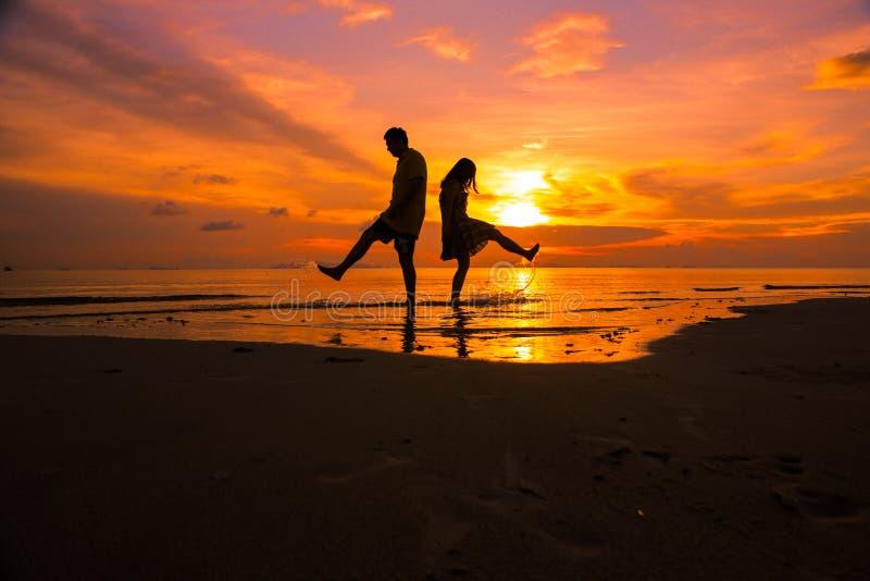 Koppla ihop p? stranden p? solnedg?ngkontur-romantiker sommar royaltyfri fotografi