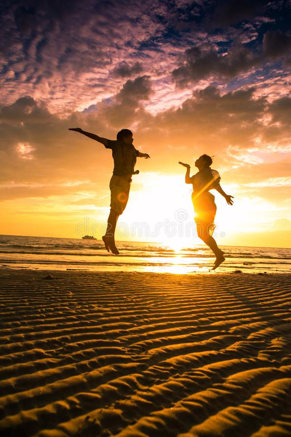 Koppla ihop p? stranden p? solnedg?ngkontur-romantiker sommar arkivbild