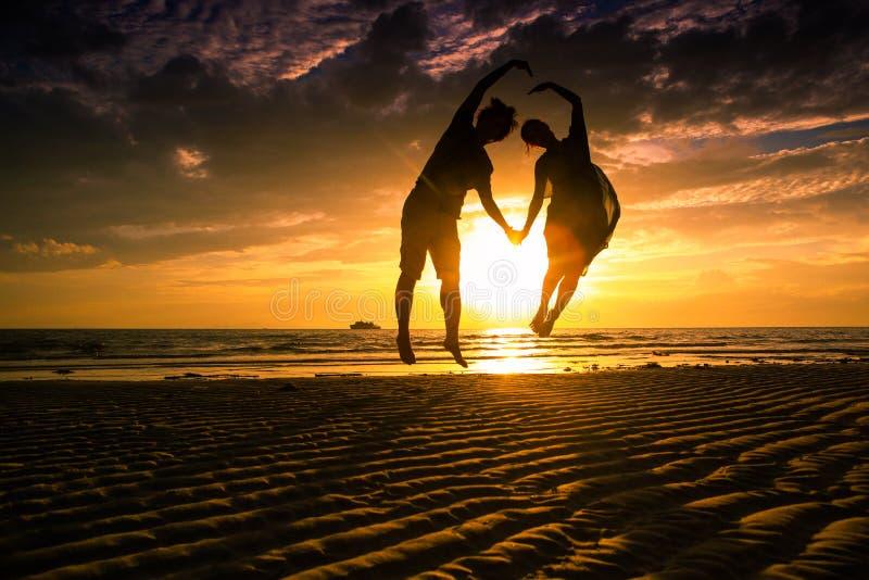 Koppla ihop p? stranden p? solnedg?ngkontur-romantiker sommar royaltyfria bilder