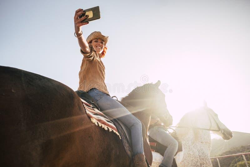 Koppla ihop ridninghästar tar en selfie med den moderna teknologismartphonen cowboylivsstil- och leendekvinna solnedgångtid och p royaltyfri foto
