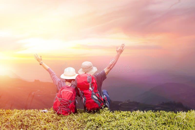 Koppla ihop ryggsäcken som tycker om solnedgång på maximum av det dimmiga berget royaltyfri bild