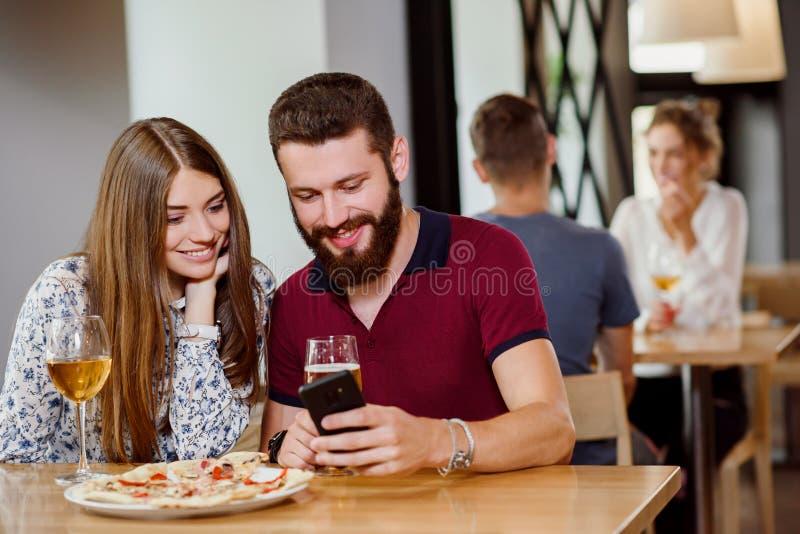 Koppla ihop sammanträde i pizzeria med pizza, vin och öl arkivfoton