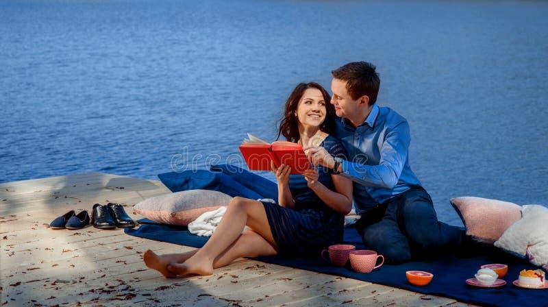 Koppla ihop sammanträde och läsning på terrass nära vattnet fotografering för bildbyråer
