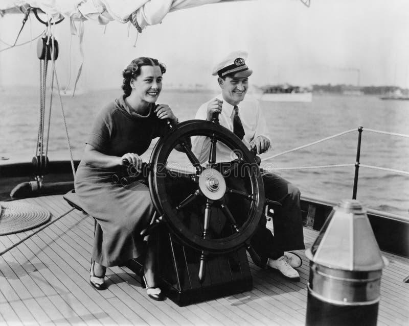 Koppla ihop sammanträde på däcket av en segelbåt som styr fartyget (alla visade personer inte är längre uppehälle, och inget gods royaltyfri foto