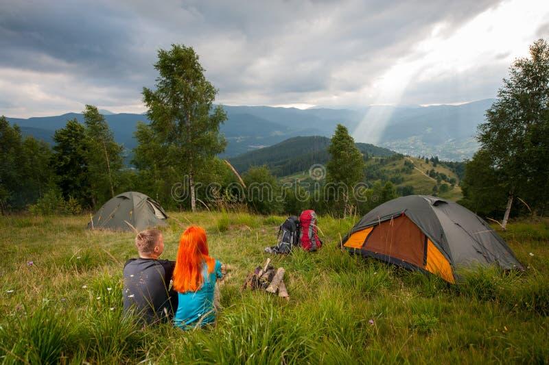 Koppla ihop sammanträde på det gröna gräset nära lägereld, tält, ryggsäckar royaltyfri fotografi