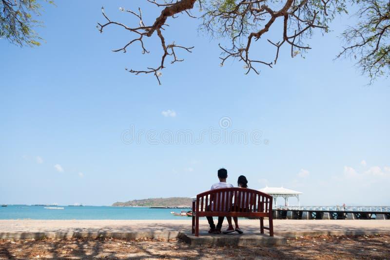 Koppla ihop sammanträde på en bänk under ett träd royaltyfria bilder