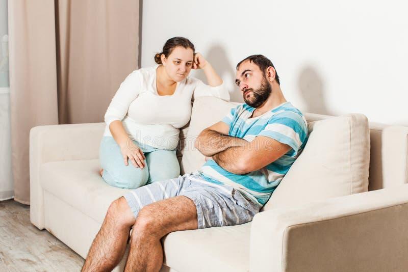 Koppla ihop sammanträde på soffan hemma i vardagsrummet royaltyfria foton