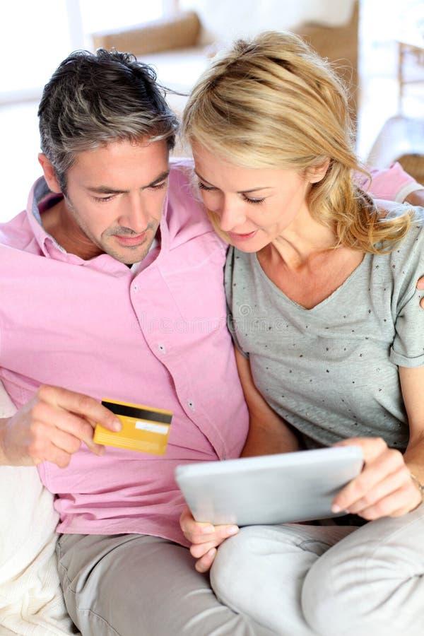 Koppla ihop sammanträde på soffan och köpande med kreditkorten arkivfoto