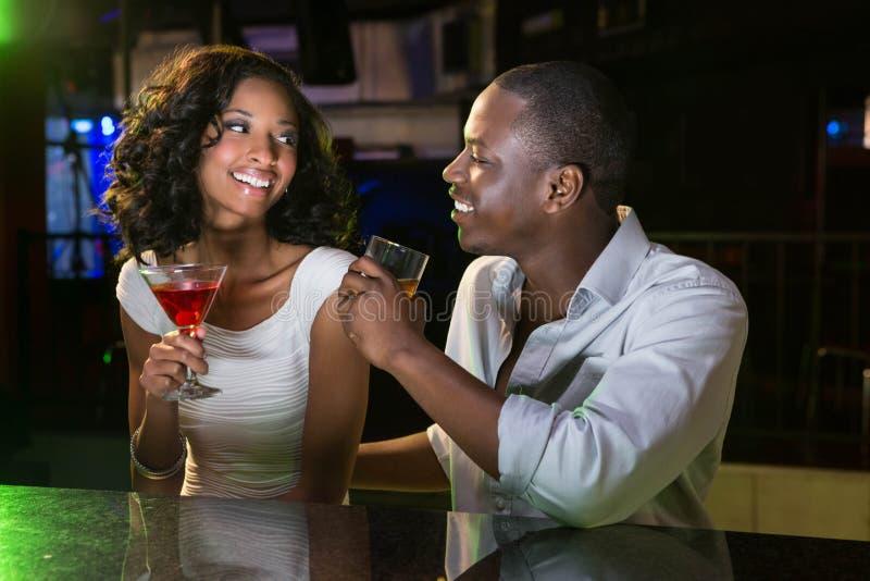 Koppla ihop samtal och att le, medan ha drinkar på stången kontra royaltyfri fotografi