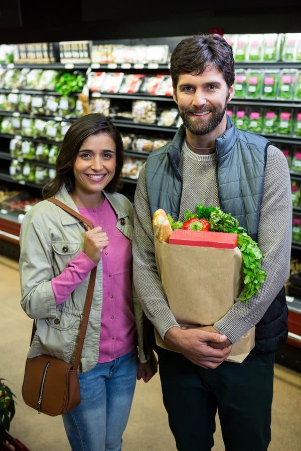 Koppla ihop shopping för grönsaker i organiskt avsnitt av supermarket arkivfoto