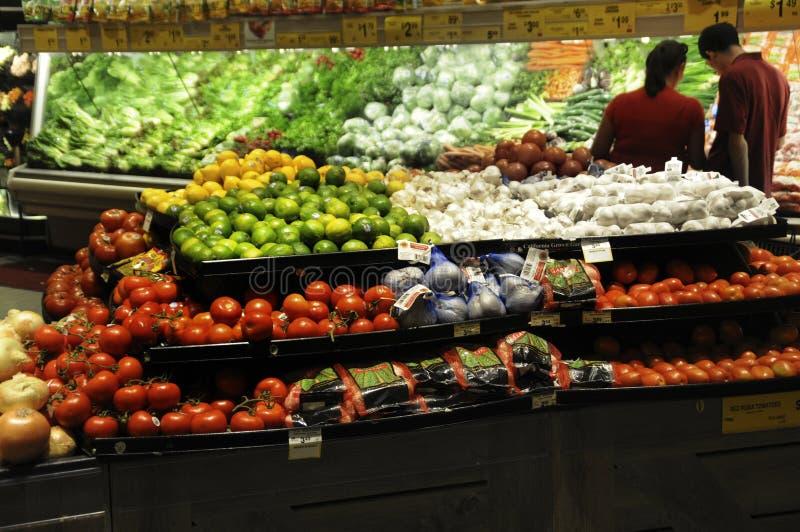 Koppla ihop shopping i frukt- och grönsakavsnittet av ett lager royaltyfri foto