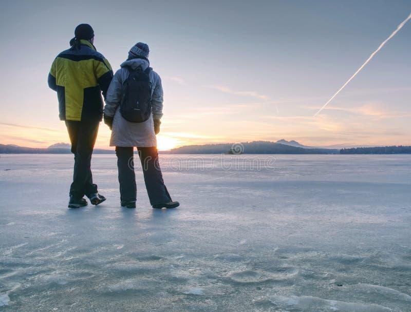 Koppla ihop staget på djupfrysta sjö- och hållhänder fotografering för bildbyråer
