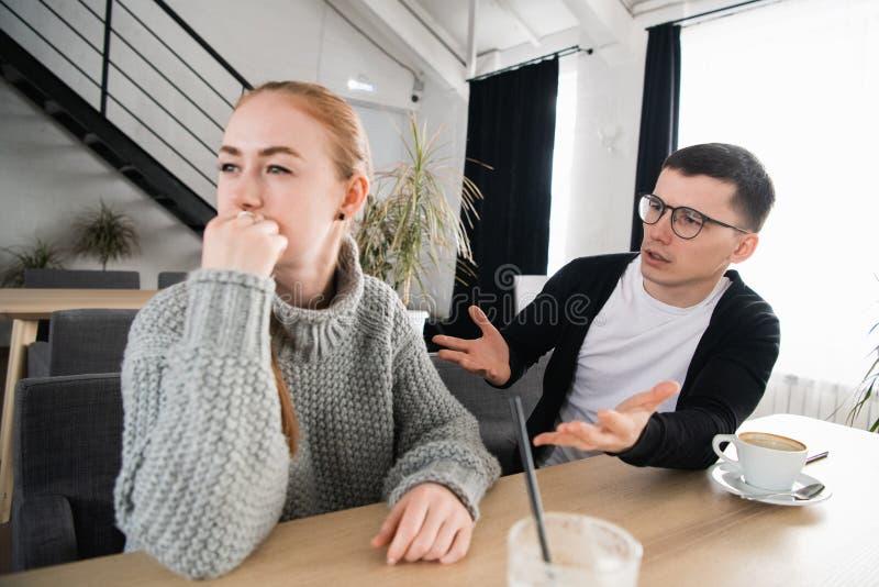 Koppla ihop stridighet En ung man försöker att ha en konversation, medan han har ignorerats av hans flickvän royaltyfri fotografi