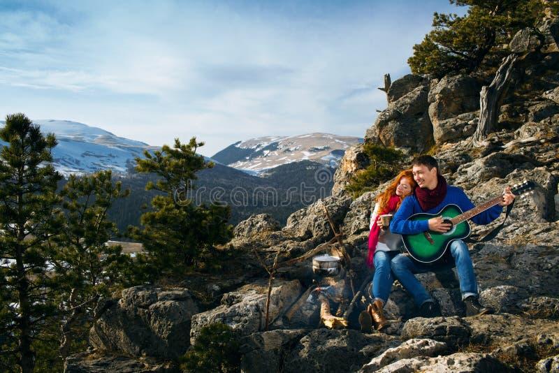 Koppla ihop turister kvinna och mansammanträde på lägret i skog och royaltyfri fotografi