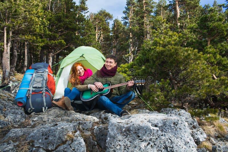 Koppla ihop turister kvinna och mansammanträde på lägret i skog och arkivbild