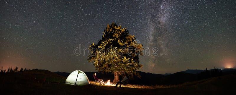Koppla ihop turister på nattlägret i berg under stjärnklar himmel arkivfoto