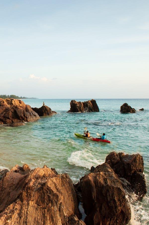 Koppla ihop turister som kayaking i det tropiska havet i aftonen Den härliga fjärden, sten, vaggar och vinkar Fiskare och solnedg arkivbild