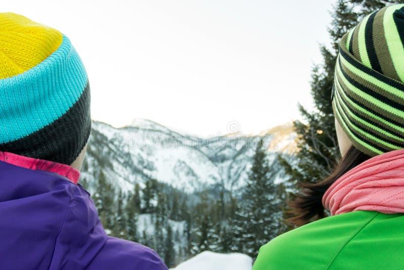 Koppla ihop turistflickor som sitter på en bänk i vintern och ser bergen royaltyfri bild