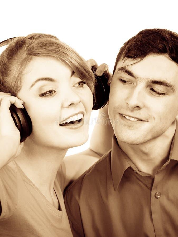 Koppla ihop två vänner med hörlurar som lyssnar till musik royaltyfria foton