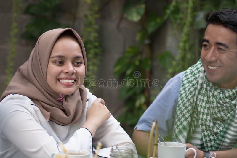 Koppla ihop unga muslim som har konversation i mitt av lunch och, frukostera utomhus- royaltyfri foto
