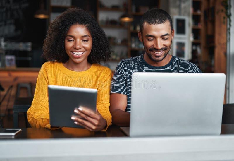 Koppla ihop upptaget, i att använda elektroniska apparater på kafét royaltyfri foto