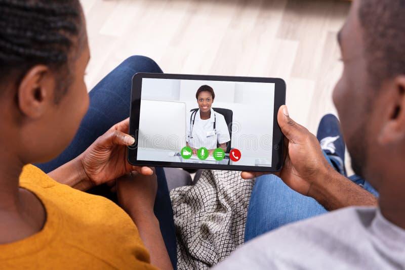Koppla ihop videoConferencing med doktor On Digital Tablet arkivbild