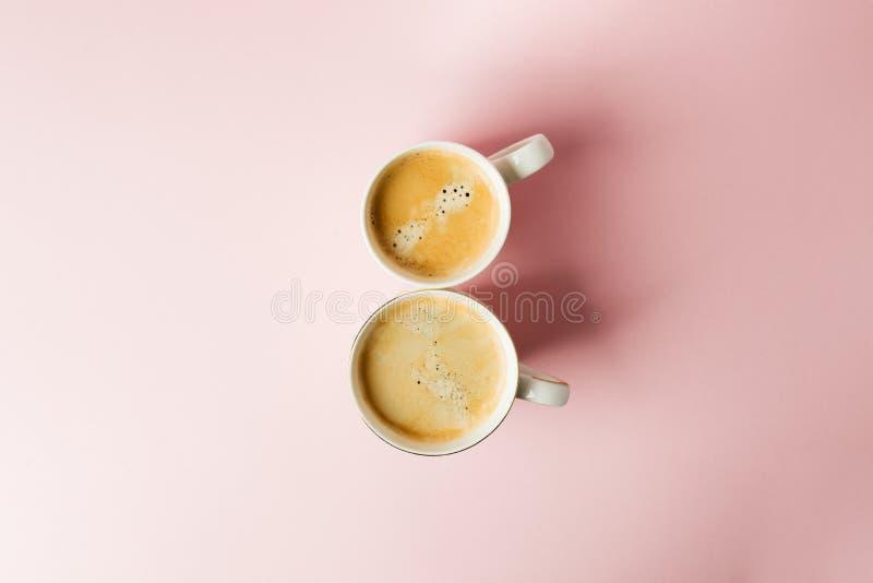 Koppla ihop vita koppar med kaffe på rosa pastellfärgad bakgrund, 8 begrepp för beröm för marsch minsta kopiera avstånd Top beskå royaltyfri bild