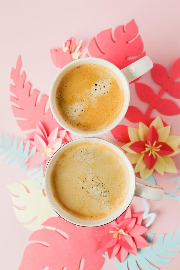 Koppla ihop vita koppar med kaffe på rosa pastellfärgad bakgrund med blommor för det pappers- hantverket för origami moderna, 8 m arkivfoto