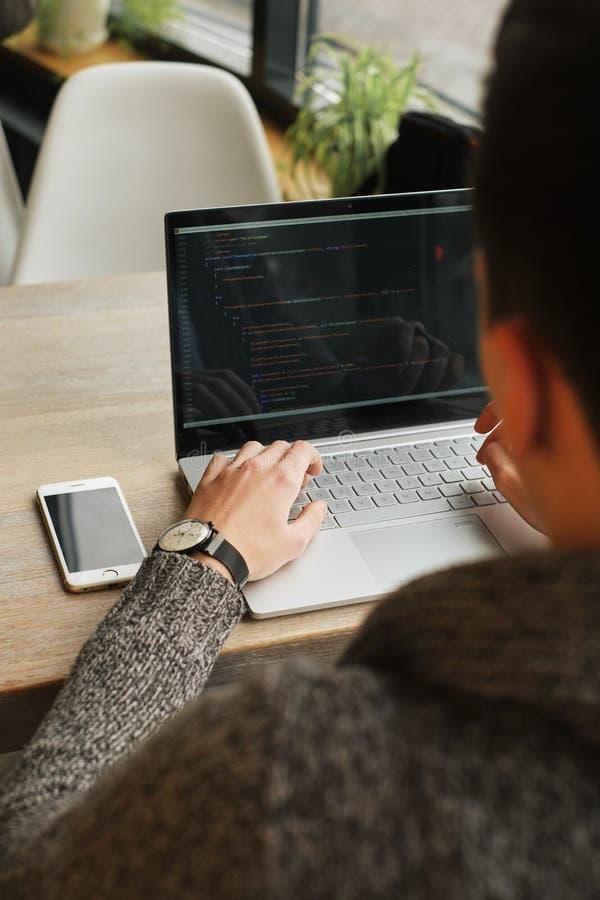 Kopplad av ung man för yrkesmässig programmerare som surfar internet på hans bärbar dator i ett kafé, smartphone på tabellen royaltyfri fotografi