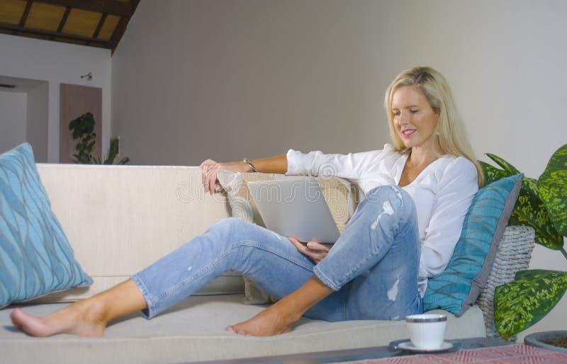 Kopplade av den tidiga 40-tal för härlig och lycklig elegant blond kvinna hemmastadd vardagsrum genom att använda internet på fun arkivfoto