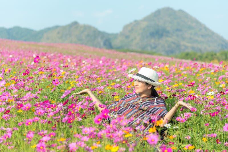 Kopplar av den asiatiska kvinnan för handelsresanden och frihet i härlig blommande kosmosblommaträdgård royaltyfri foto