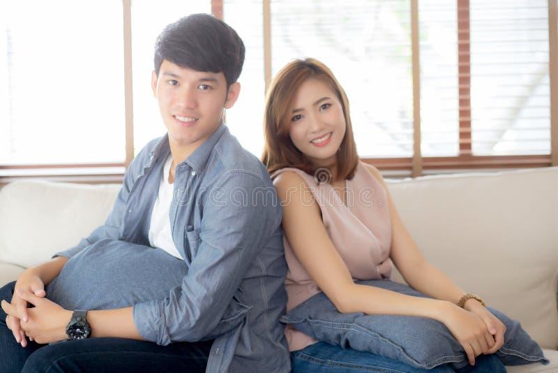Kopplar av tillfredsst?llde unga asiatiska par f?r h?rlig st?ende och tillsammans i vardagsrum hemma arkivbild