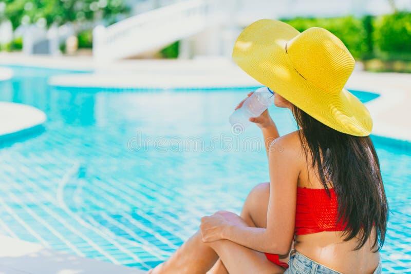 Kopplar av tonårigt dricka kallt vatten för flickan på simbassängen arkivfoton