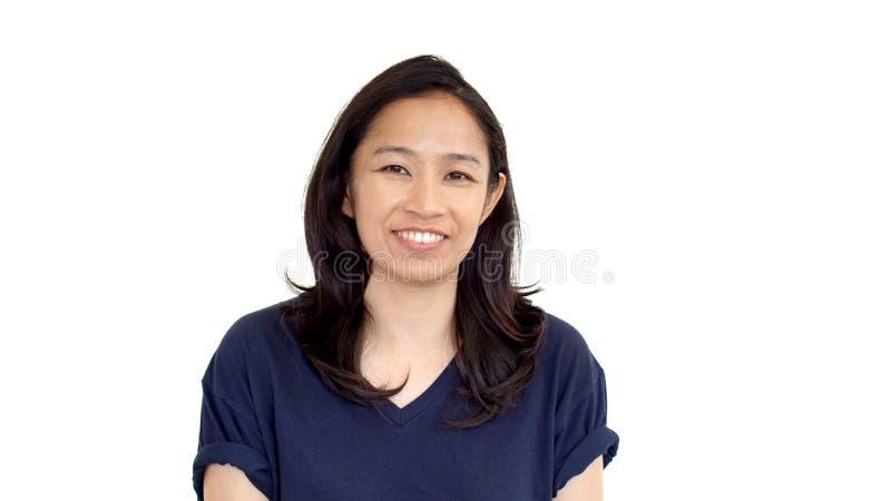 Kopplar av vit bakgrund för den tillfälliga asiatiska flickan som ler framsidan med, utslagsplats s arkivfoton